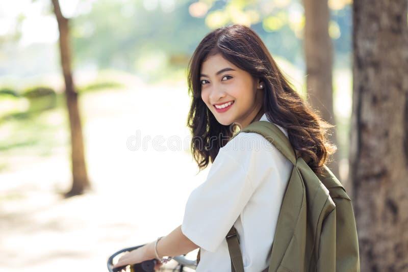 Mujer joven que monta una bici en un parque del verano Forma de vida de la mujer concentrada fotos de archivo libres de regalías