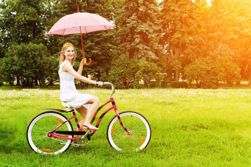 Mujer joven que monta una bicicleta imagenes de archivo