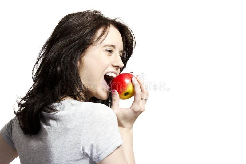 Mujer joven que muerde en manzana roja fotografía de archivo