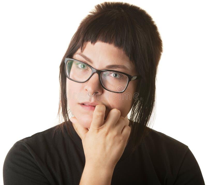 Mujer joven que muerde sus uñas fotografía de archivo