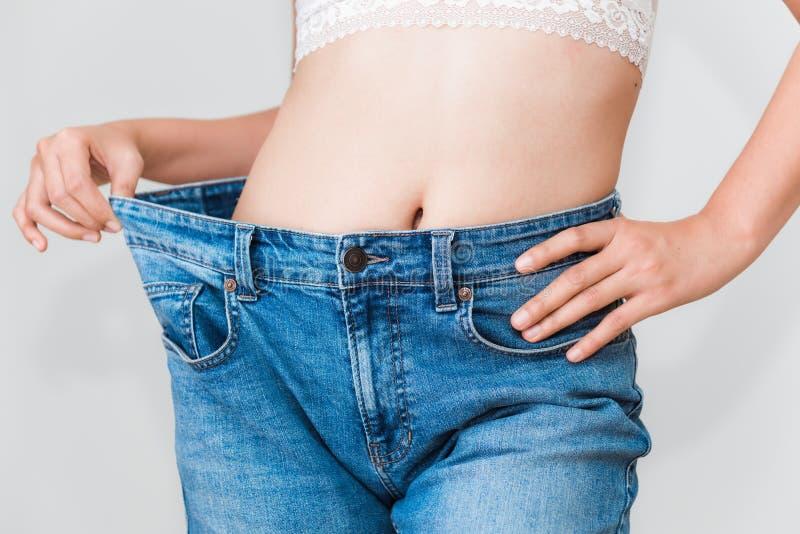 Mujer joven que muestra la pérdida de peso acertada con sus vaqueros, Healt imagenes de archivo