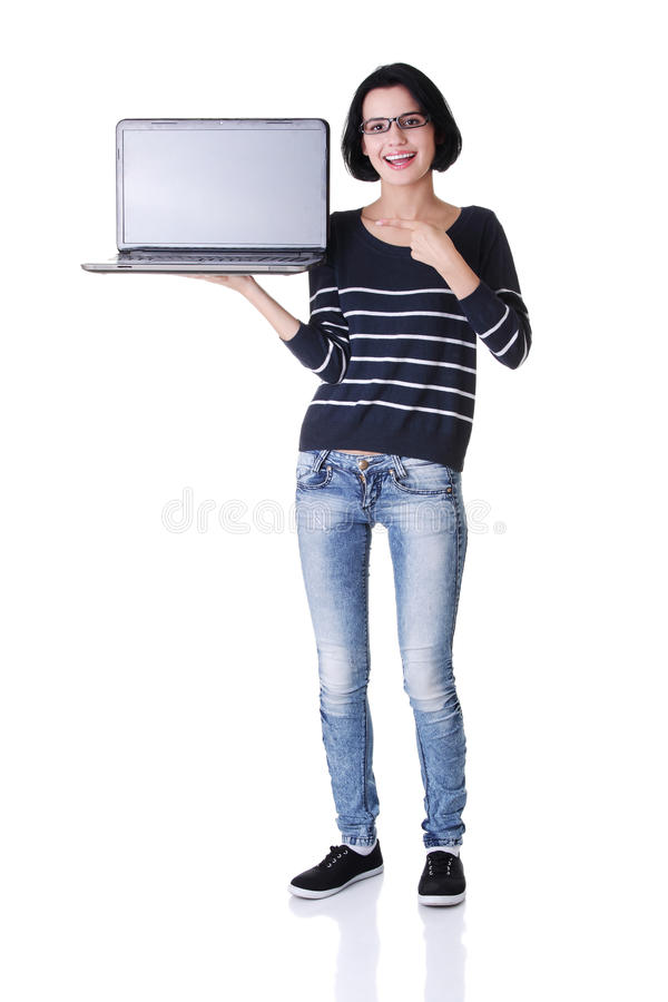Mujer joven que muestra la pantalla de la computadora portátil de 17 pulgadas imágenes de archivo libres de regalías