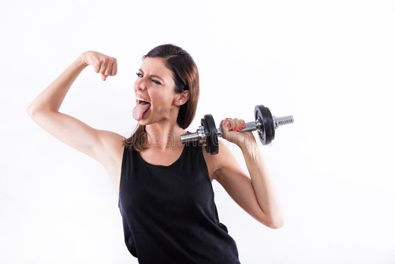Mujer joven que muestra los músculos foto de archivo libre de regalías