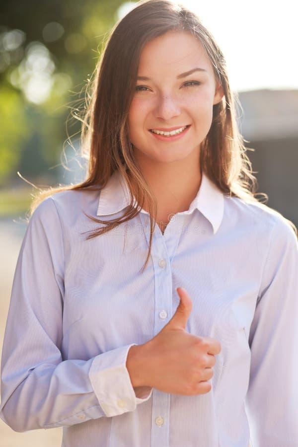 Mujer joven que muestra los pulgares para arriba foto de archivo libre de regalías