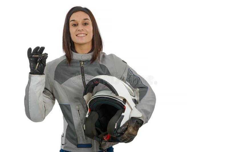 Mujer joven que muestra orgulloso su nueva licencia de la motocicleta en blanco foto de archivo