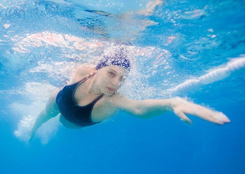 Mujer joven que nada el arrastre delantero en una piscina, tomada bajo el agua imagenes de archivo