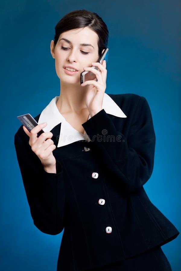 Mujer joven que paga con de la tarjeta de crédito por el teléfono imágenes de archivo libres de regalías