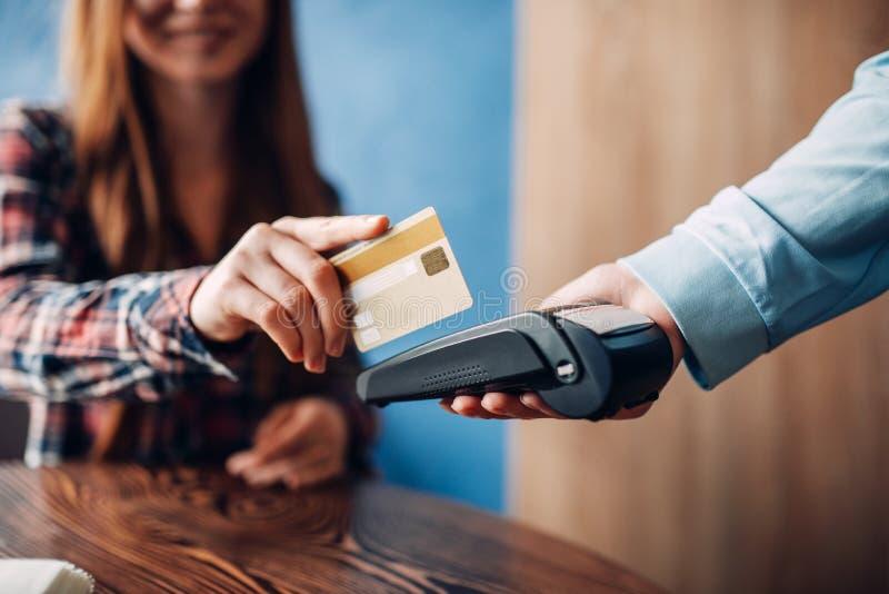 Mujer joven que paga con la tarjeta de crédito en café fotos de archivo libres de regalías