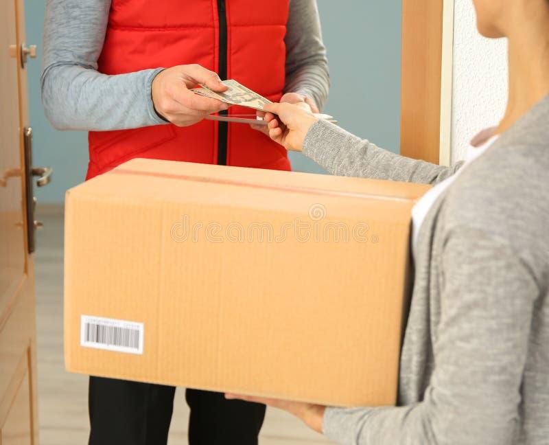 Mujer joven que paga el paquete recibido imagen de archivo