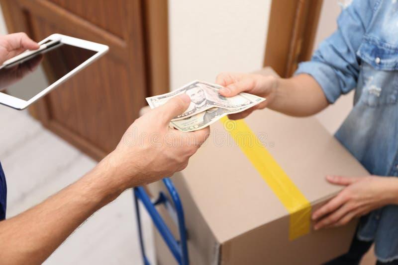 Mujer joven que paga el paquete recibido de mensajero, foto de archivo