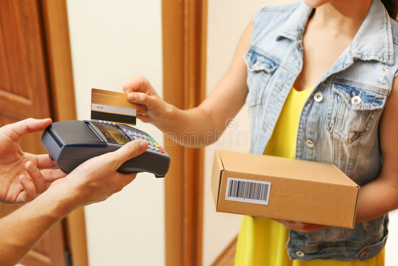 Mujer joven que paga el paquete recibido de mensajero foto de archivo