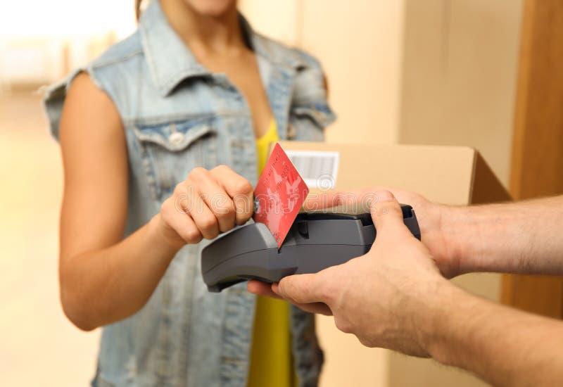 Mujer joven que paga el paquete recibido de mensajero imagen de archivo