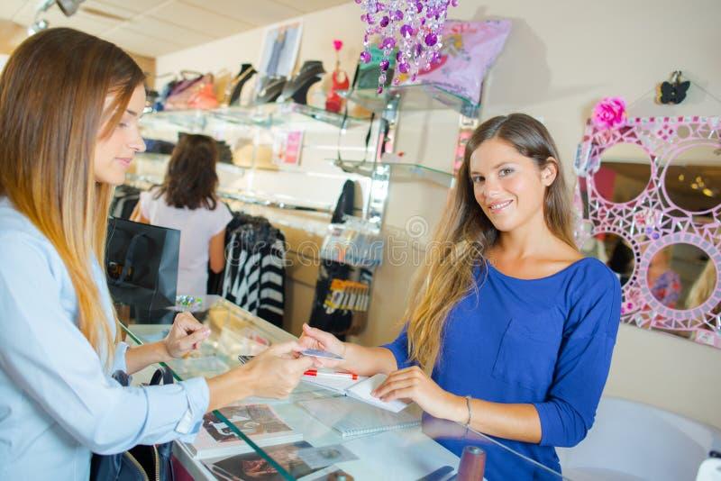 Mujer joven que paga en tienda imagen de archivo libre de regalías