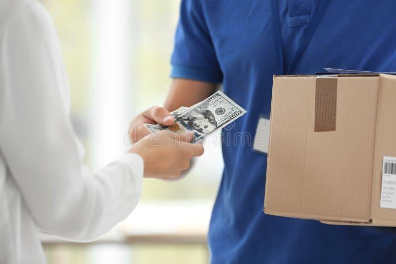 Mujer joven que paga paquete entregado dentro imagen de archivo