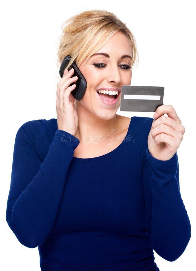Mujer joven que paga por el teléfono celular de la tarjeta de crédito y imagen de archivo