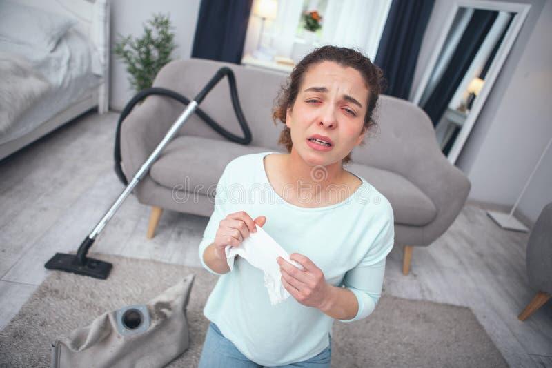 Mujer joven que parece al enfermo y que siente alérgica para sacar el polvo imagen de archivo libre de regalías