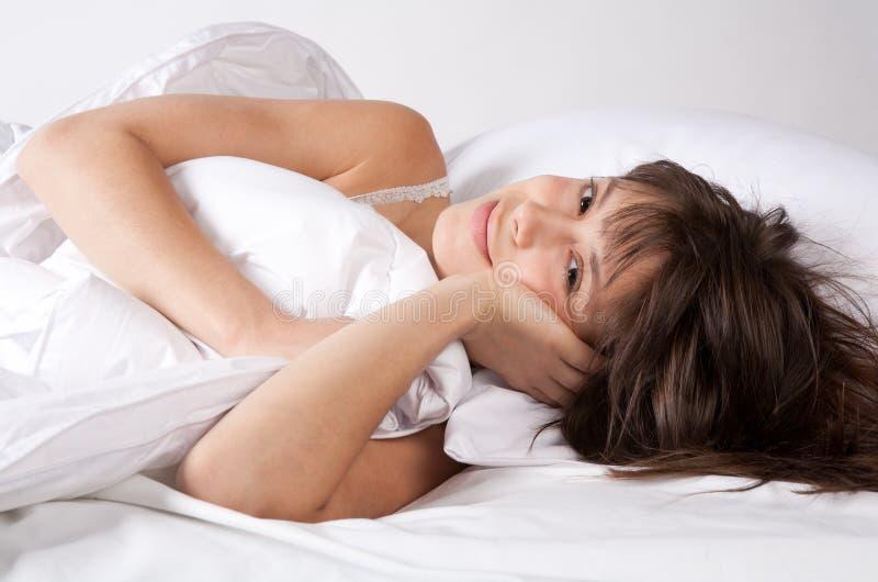 Mujer joven que parece Comfy en cama foto de archivo