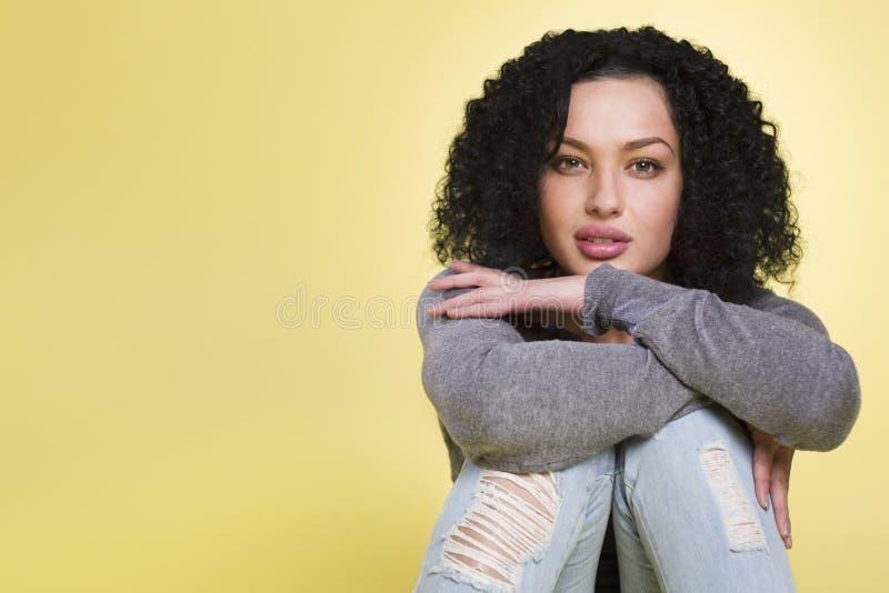 Mujer joven que parece sensual en fondo amarillo imagenes de archivo