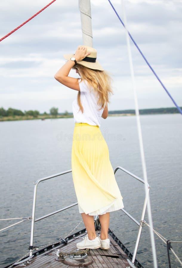 Mujer joven que permanece en el velero, navegando, cielo nublado imágenes de archivo libres de regalías