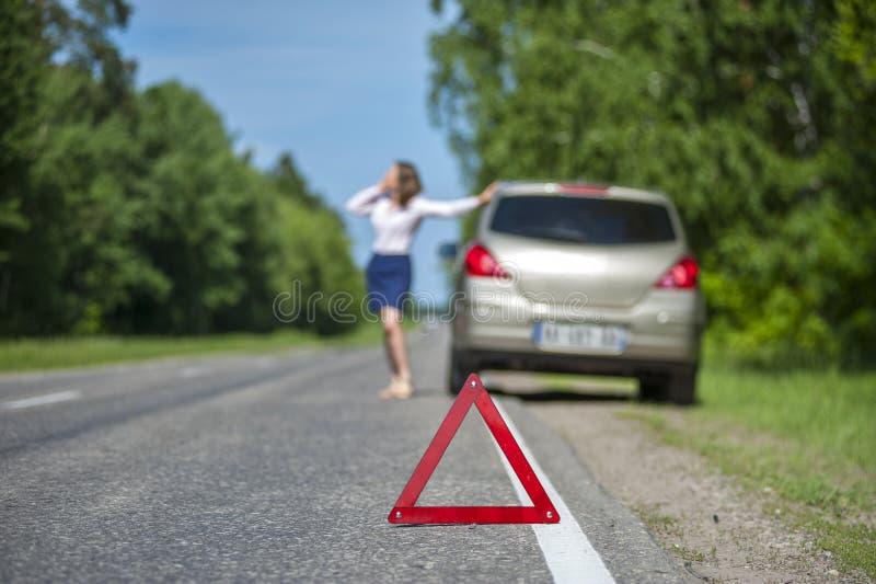 Mujer joven que pide ayuda del coche después de avería en el ro imagenes de archivo