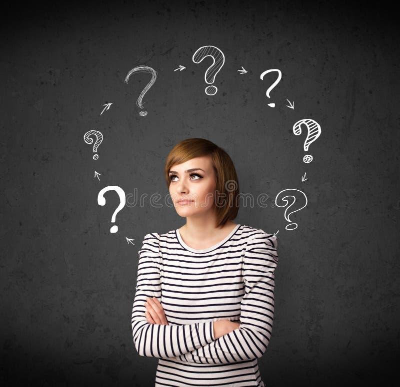 Mujer joven que piensa con la circulación del signo de interrogación alrededor de su h imagenes de archivo
