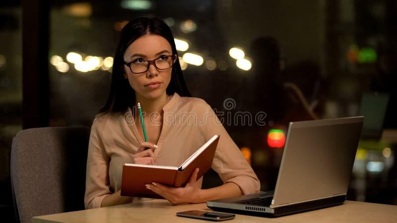 Mujer joven que piensa sobre las ideas de lanzamiento, escribiendo el plan empresarial en cuaderno foto de archivo