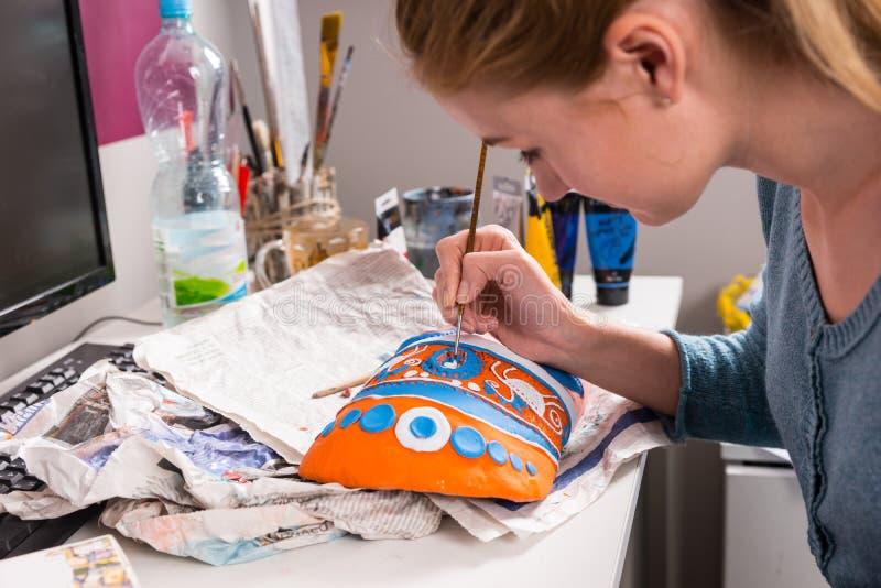 Mujer joven que pinta una máscara colorida fotos de archivo