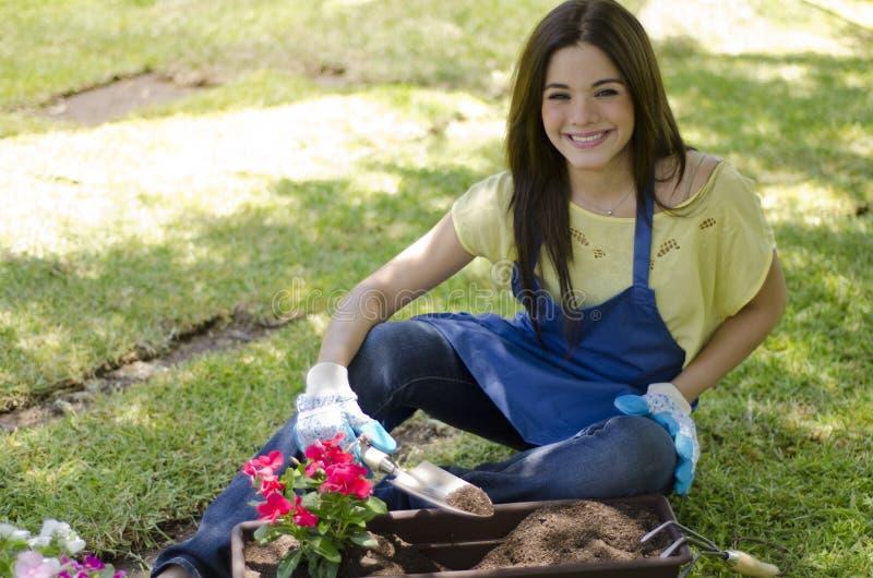Mujer joven que planta algunas flores imagenes de archivo