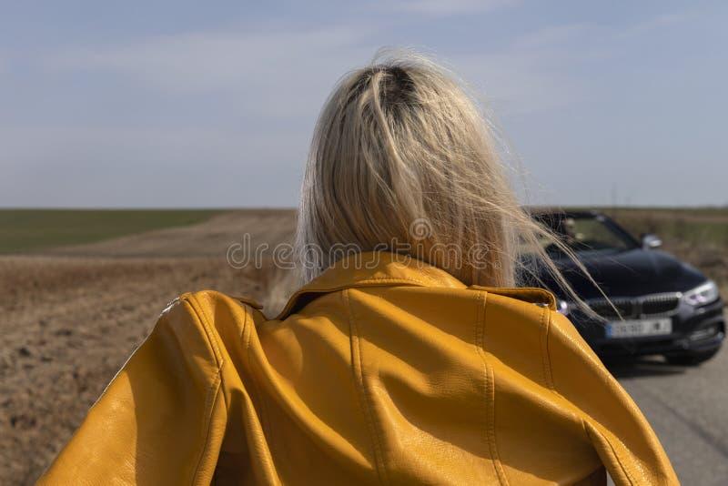 Mujer joven que plantea inclinarse en el coche convertible imagenes de archivo