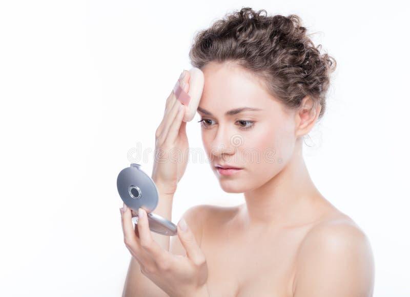 Mujer joven que pone la fundación del polvo en su cara imagen de archivo libre de regalías