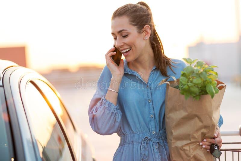 Mujer joven que pone los ultramarinos en el tronco de coche imagenes de archivo