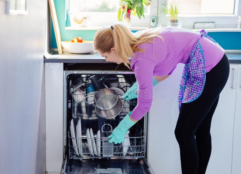 Mujer joven que pone platos sucios al lavaplatos imágenes de archivo libres de regalías