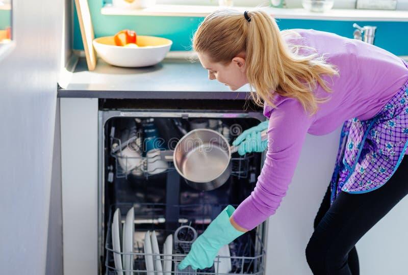 Mujer joven que pone platos sucios al lavaplatos fotografía de archivo libre de regalías