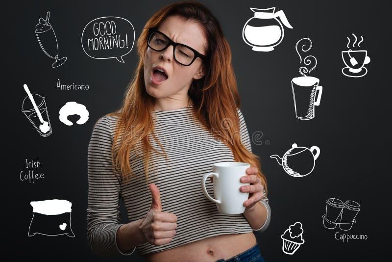 Mujer joven que pone su pulgar mientras que goza de su café de la mañana fotos de archivo