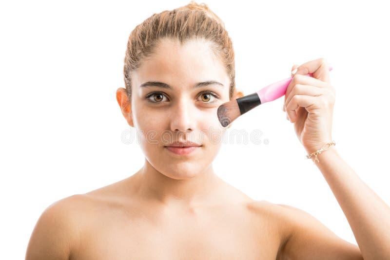 Mujer joven que pone un cierto maquillaje imagen de archivo