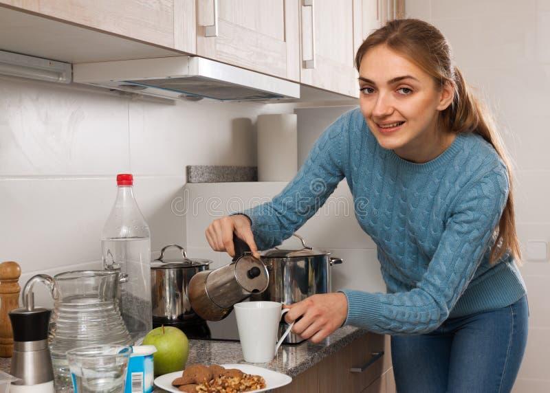 Mujer joven que prepara el café en la cocina en casa fotos de archivo libres de regalías