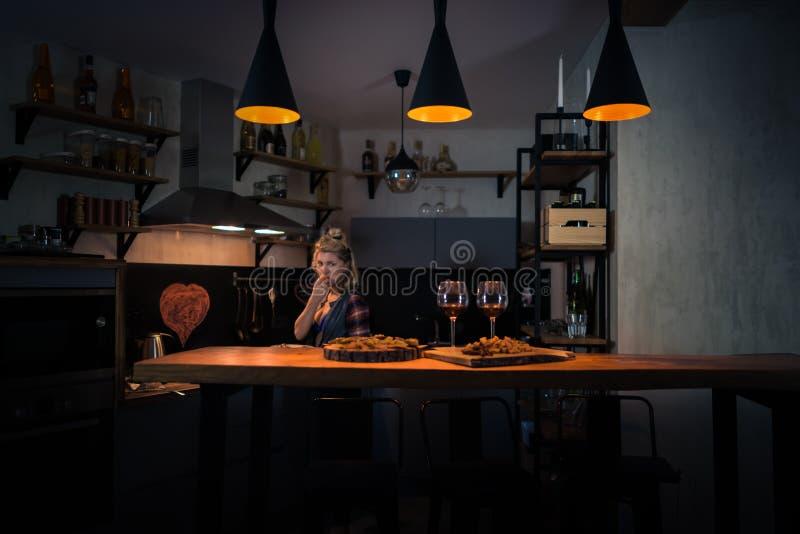 Mujer joven que prepara la cena en la cocina casera moderna fotos de archivo