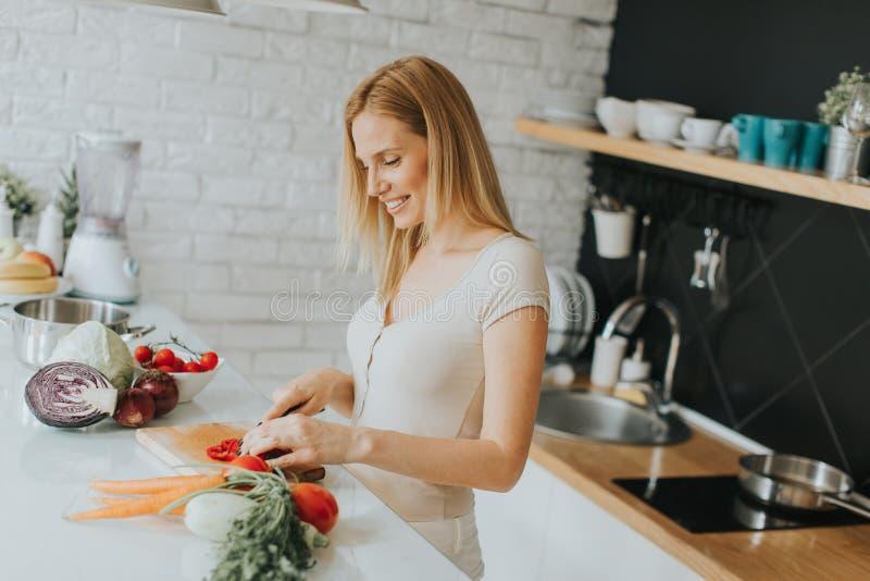 Mujer joven que prepara la comida sana en la cocina moderna imagenes de archivo