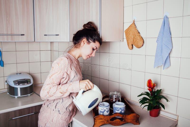 Mujer joven que prepara té en la cocina Agua de colada en una taza imagen de archivo