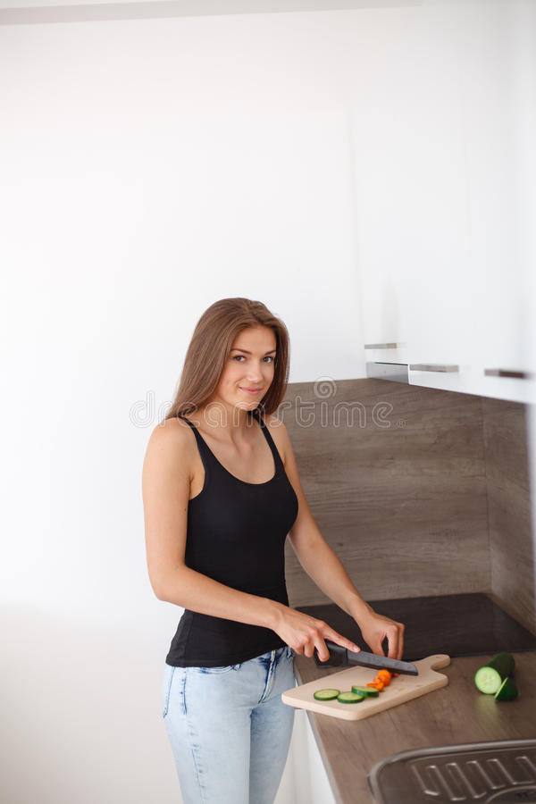 Mujer joven que prepara una comida sana de verduras frescas y de frutas foto de archivo libre de regalías