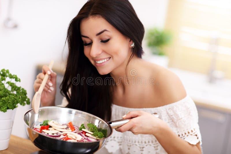 Mujer joven que prepara verduras fritas en cocina imagen de archivo