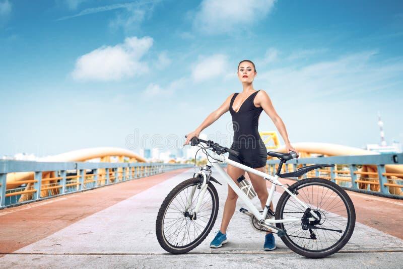 Mujer joven que presenta con la bicicleta imagen de archivo