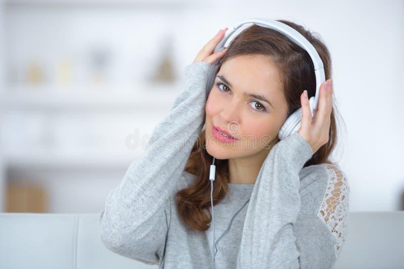 Mujer joven que presenta con las auriculares encendido fotografía de archivo libre de regalías