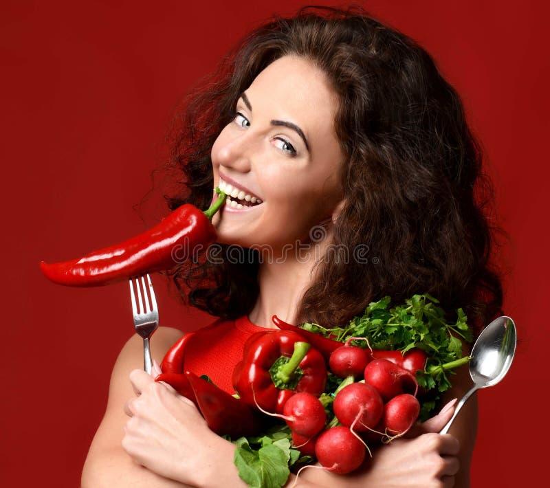 Mujer joven que presenta con verde rojo fresco de la pimienta del rábano de las verduras fotografía de archivo