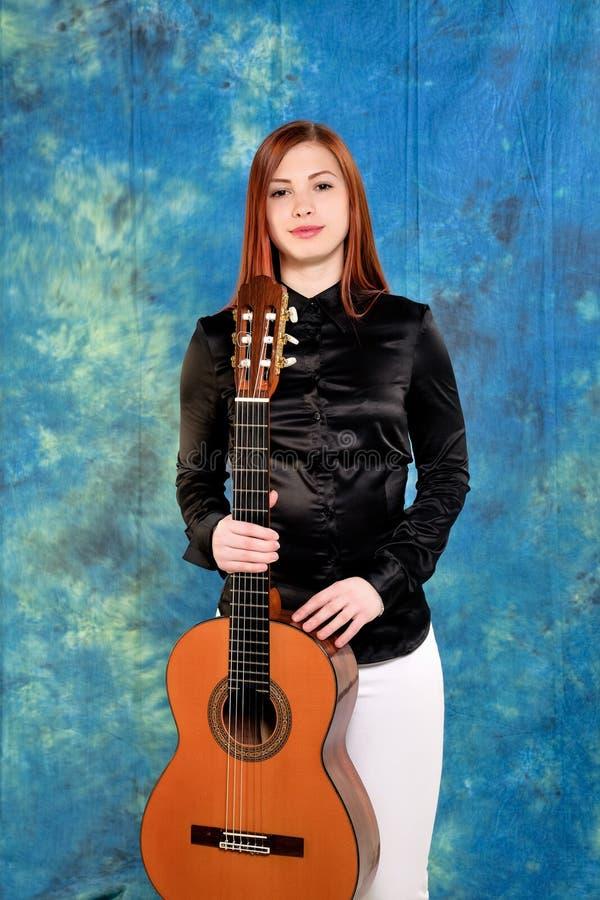 Mujer joven que presenta en el estudio que sostiene una guitarra clásica fotos de archivo libres de regalías