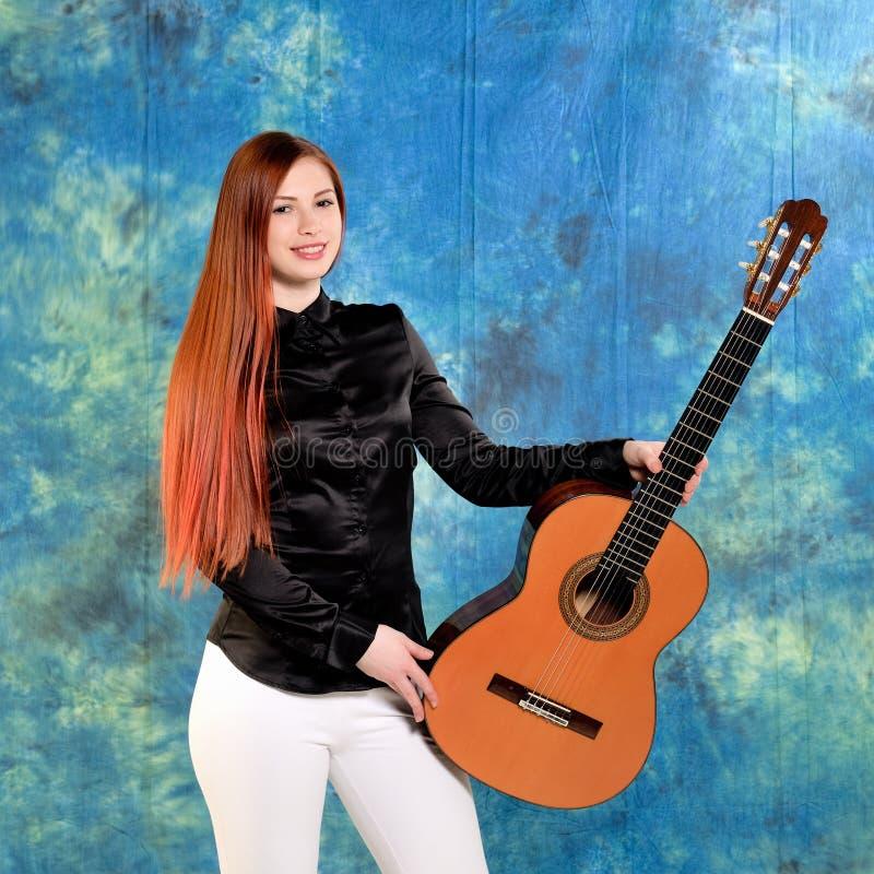 Mujer joven que presenta en el estudio que sostiene una guitarra clásica fotografía de archivo libre de regalías