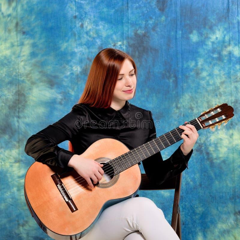 Mujer joven que presenta en el estudio que sostiene una guitarra clásica imagen de archivo