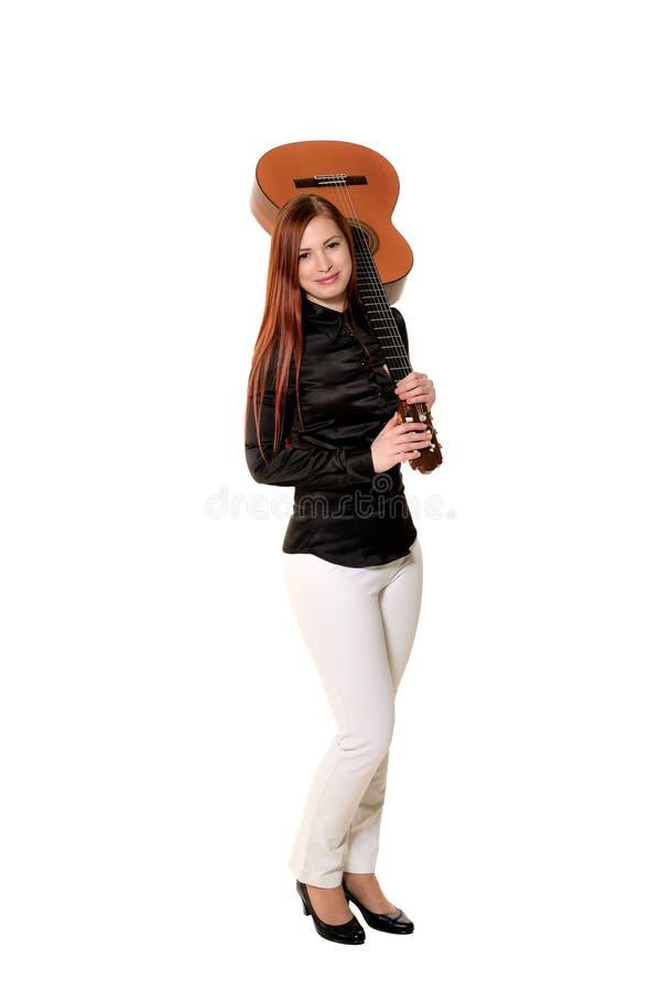 Mujer joven que presenta en el estudio que sostiene una guitarra clásica imagenes de archivo