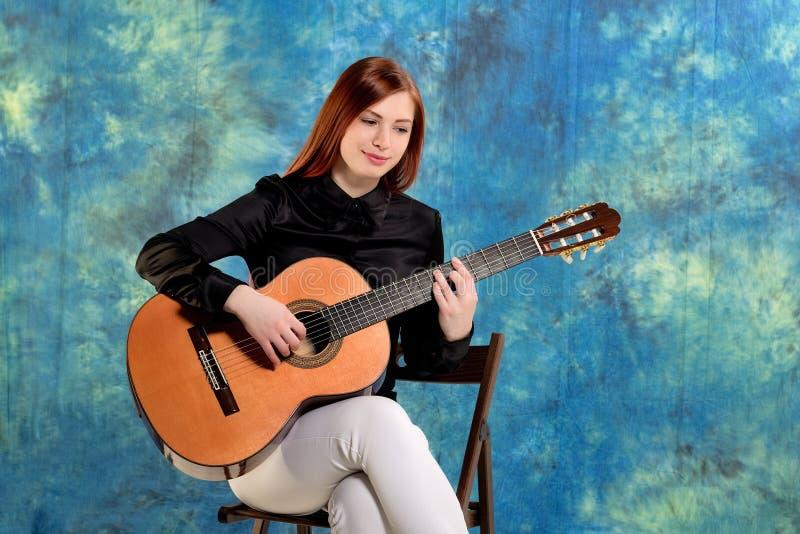 Mujer joven que presenta en el estudio que sostiene una guitarra clásica foto de archivo