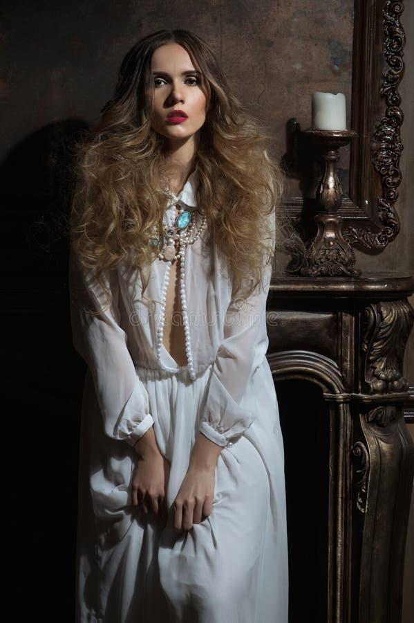 Mujer joven que presenta en el vestido blanco con joyería imagenes de archivo